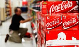 An employee arranges bottles of Coca-Cola at a store in Alexandria, Virginia October 16, 2012. REUTERS/Kevin Lamarque/Files