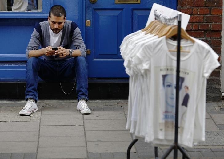 A man uses his mobile phone next to a rail of clothes for sale in central London August 10, 2013. REUTERS/Luke MacGregor/Files