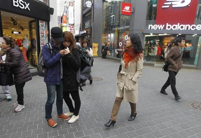 A couple checks a picture after taking photos with a mobile phone as people walk to shop in central Seoul April 8, 2013. REUTERS/Lee Jae-Won/Files