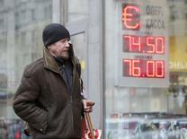 Мужчина проходит мимо вывески пункта обмена валюты в Москве 11 февраля 2015 года. Рубль в минусе на торгах среды - участники рынка пока предпочитают безопасные инструменты в условиях неопределенности итогов переговоров на высшем уровне о прекращении насилия на востоке Украины, хотя последние новости и повышают вероятность заключения мира. REUTERS/Sergei Karpukhin