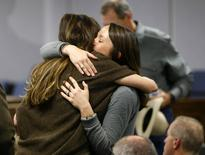 Taya Kyle (L), wife of slain Navy SEAL Chris Kyle, hugs a family member after they arrive for the opening day of the capital murder trial of former Marine Eddie Ray Routh at the Erath County Donald R. Jones Justice Center in Stephenville, Texas February 11, 2015. REUTERS/Tom Fox/Pool