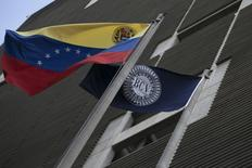 Flags of Venezuela (L) and the Central Bank are seen at the central bank building in Caracas February 10, 2015. REUTERS/Jorge Silva