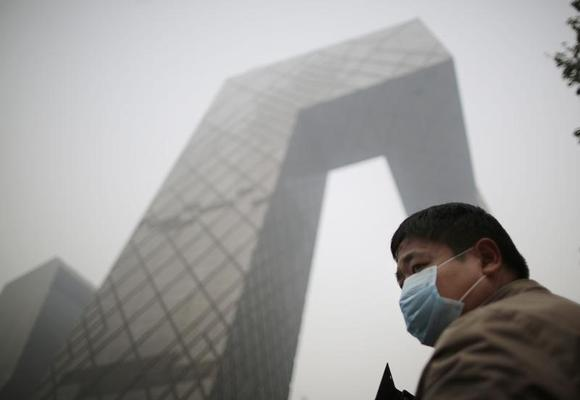 A man wearing a mask walks on a street on a hazy day in Beijing in this file photo taken on October 24, 2014. REUTERS/Kim Kyung-Hoon