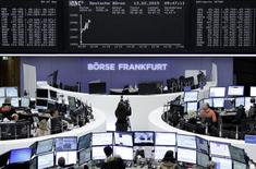 Traders are pictured at their desks in front of the DAX board at the Frankfurt stock exchange February 13, 2015 after the DAX index crossed the 11.000 mark.      REUTERS/Staff/remote