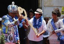 """Rio de Janeiro's Mayor Eduardo Paes (C) hands over the city's ceremonial key to the """"Rei Momo"""", or Carnival King Wilson Neto (L) at Cidade Palace in Rio de Janeiro February 13, 2015. REUTERS/Sergio Moraes"""
