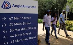 Personas caminan en las afueras de las oficinas de Anglo American en Johannesburg. Imagen de archivo, 8 enero, 2013. La minera global Anglo American anunció el viernes que sufrió una amortización de 3.900 millones de dólares, principalmente en sus operaciones de mineral de hierro en Brasil, debido a la caída en los precios de las materias primas, aunque al mantener los dividendos tranquilizó a los inversores.  REUTERS/Siphiwe Sibeko