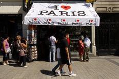 Tourists walk past a souvenir shop on the Champs-Elysees in Paris, August 6, 2009. REUTERS/Benoit Tessier