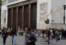 Personas caminan frente al edificio del Banco Central de Colombia en la ciudad de Bogotá. Imagen de archivo, 20 agosto, 2014. El Banco Central de Colombia mantendría sin cambios su tasa de interés en un 4,5 por ciento en su reunión de política monetaria del viernes, en medio de perspectivas de desaceleración de la economía, mostró el lunes un sondeo de Reuters. REUTERS/John Vizcaino
