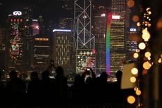 Personas sacan fotografías del distrito financiero de Hong Kong. Imagen de archivo, 12 febrero, 2015.  El crecimiento económico de China podría desacelerarse a entre un 6,9 y un 7,1 por ciento este año, en momentos en que el país se defiende de los riesgos de una deflación, dijo el martes el jefe del gabinete de estudios del banco central de China. REUTERS/Bobby Yip