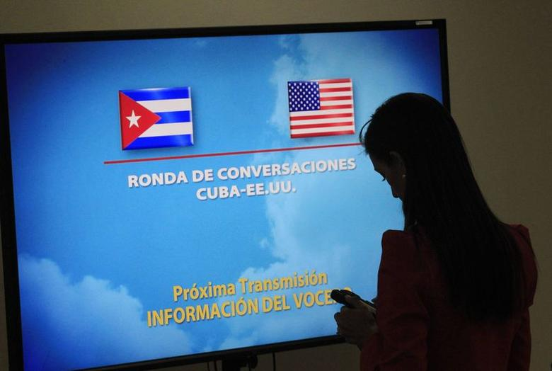 A journalist stands near a screen announcing a round of negotiations between Cuba and the U.S. in Havana January 22, 2015.  REUTERS/Stringer