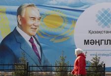 Женщина проходит мимо плаката, на котором изображен президент Казахстана Нурсултан Назарбаев в Алма-Ате 16 февраля 2015 года. Бессменный лидер Казахстана Нурсултан Назарбаев и его представители не отреагировали публично на развернутую в последнюю неделю в лояльных политических кругах и прессе кампанию в поддержку его 26-летних полномочий на еще один президентский срок. REUTERS/Shamil Zhumatov