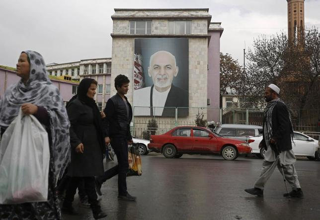 People walk past a picture of Afghan President Ashraf Ghani on a street in Kabul February 19, 2015. REUTERS/Omar Sobhani