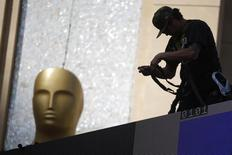 A worker hangs lights next to an Oscar statue outside the Dolby Theatre. REUTERS/Lucy Nicholson