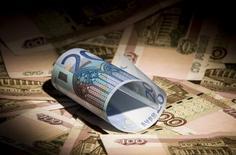 Банкноты по 100 рублей и 20 евро. Москва, 17 февраля 2014 года. Рубль начал ростом пятничные биржевые торги на фоне дорожающей нефти и в преддверии уплаты крупных налогов к середине следующей недели. REUTERS/Maxim Shemetov