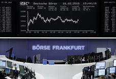 Traders are pictured at their desks in front of the DAX board at the Frankfurt stock exchange February 18, 2015. REUTERS/Staff/remote