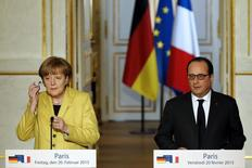 Канцлер Германии Ангела Меркель и президент Франции Франсуа Олланд на совместной пресс-конференции в Париже. 20 февраля 2015 года. Новые санкции против России возможны, если мирное соглашение о прекращении конфликта на востоке Украины будет нарушено, однако они не являются целью, сказала в пятницу канцлер Германии Ангела Меркель. REUTERS/Pascal Rossignol