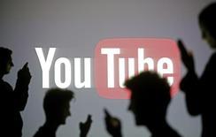 Personas posan frente al logo de Youtube en Zenica. Imagen de archivo, 19 octubre, 2014.  Youtube lanzará la próxima semana una nueva aplicación para niños, que funcionará en smartphones y tabletas y que se centrará en contenido apropiado para el público infantil. REUTERS/Dado Ruvic
