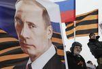 Люди держат постер с изображением президента России Владимира Путина на митинге в Ставрополе 21 февраля 2015 года. Президент РФ Владимир Путин считает, что война между Россией и Украиной вряд ли возможна и надеется, что до нее никогда не дойдет. REUTERS/Eduard Korniyenko