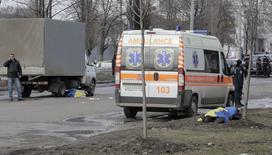 Жертвы взрыва, накрытые флагами Украины, в Харькове 22 февраля 2015 года. Как минимум два человека погибли и более десяти получили ранения в результате взрыва, произошедшего в воскресенье в гуще участников проукраинского марша в Харькове, далеко от зоны военных действий на востоке Украины, сообщила милиция. REUTERS/Stanislav Belousov