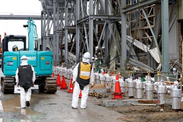 Workers wearing radiation protective gear stand outside of the No. 4 reactor building at TEPCO's tsunami-crippled Fukushima Daiichi nuclear power plant in Fukushima prefecture, November 12, 2014. REUTERS/Shizuo Kambayashi/Pool