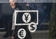 Символы иены, доллара и евро возле банка в Токио. 27 ноября 2014 года. Курс доллара к иене снижается, после того как председатель ФРС Джанет Йеллен дала понять, что центробанк не спешит повышать процентные ставки. REUTERS/Issei Kato