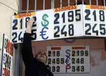 Сотрудник пункта обмена валюты меняет курс в Тбилиси 23 февраля 2015 года. Грузия намерена принять ряд мер, включая продажу гособъектов, сокращение административных расходов и реструктуризацию банковских кредитов в иностранной валюте физических лиц, для борьбы с кризисом. REUTERS/David Mdzinarishvili