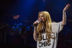 Actress Lindsay Lohan introduces singer Miley Cyrus during the 2013 Z100 Jingle Ball in New York December 13, 2013. REUTERS/Lucas Jackson