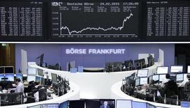 Traders are pictured at their desks in front of the DAX board at the Frankfurt stock exchange February 24, 2015.  REUTERS/Stringer/Remote
