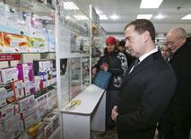 Премьер-министр РФ Дмитрий Медведев в аптеке в Уфе. 3 февраля 2015 года. Фармпроизводитель Отисифарм, который до 2014 года был частью компании Фармстандарт, увеличил выручку на 12 процентов до 16,6 миллиарда рублей в 2014 году, сообщила компания в четверг. REUTERS/Ekaterina Shtukina/RIA Novosti/Pool