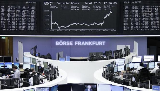 Traders are pictured at their desks in front of the DAX board at the Frankfurt stock exchange February 24, 2015.  REUTERS-Stringer-Remote
