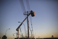 Imagen de archivo de un especialista trabajando en un poste eléctrico en Itu, Brasil, oct 27 2014. La economía de Brasil probablemente ya se encuentra en recesión y la contracción empeorará si el Gobierno se ve forzado a racionar la electricidad más adelante este año debido a una sequía, de acuerdo a la encuestadora más precisa en los sondeos de Reuters en torno a los indicadores brasileños del 2014. REUTERS/Nacho Doce