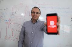 Damir Sabol, owner of software company which developed the PhotoMath application, poses with a smartphone in Zagreb February 24, 2015. REUTERS/Antonio Bronic