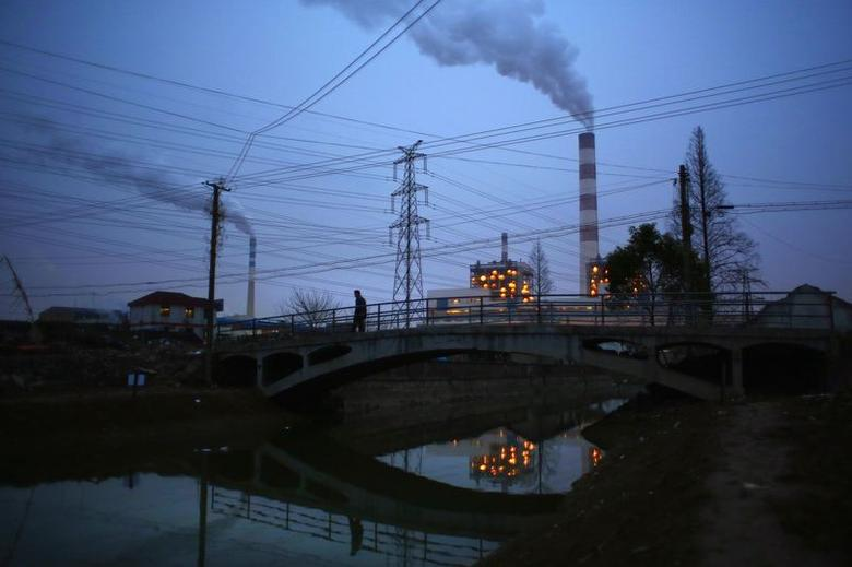 A man walks over a bridge as smoke rises from chimneys of a thermal power plant in Shanghai February 23, 2015. REUTERS/Carlos Barria