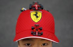 A 10 year old Ferrari fan shows his cap with miniatures of Ferrari's formula one car just after getting an autograph of his favourite driver Kimi Raikkonen of Finland, after the qualifying session of the Japanese F1 Grand Prix at the Suzuka Circuit October 4, 2014. REUTERS/Yuya Shino