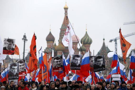People hold flags and posters during a march to commemorate Kremlin critic Boris Nemtsov, who was shot dead on Friday night, near St. Basil's Cathedral in central Moscow March 1, 2015.   REUTERS-Sergei Karpukhin