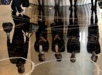 A porter carries luggage past a group of reception staff that are reflected in the floor as they stand in the foyer of the five-star rated Sofitel Hotel in Beijing in this November 19, 2007 file photo.  REUTERS/David Gray/Files