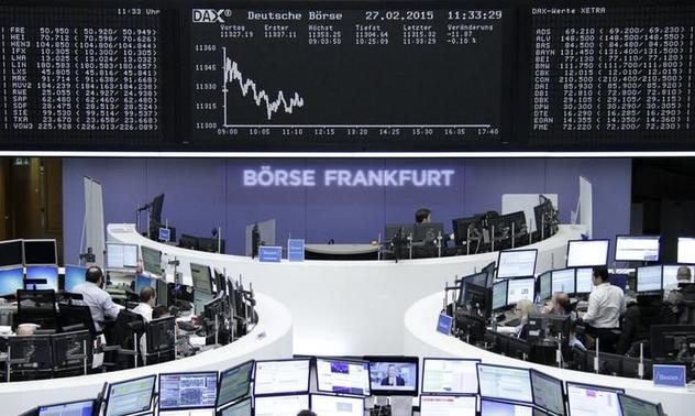 Traders are pictured at their desks in front of the DAX board at the Frankfurt stock exchange February 27, 2015. REUTERS/Pawel Kopczynski/Remote