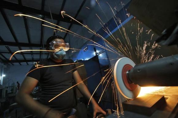 A worker operates a lathe machine as he makes a steel cutter at a manufacturing unit in Noida, on the outskirts of New Delhi November 3, 2014. REUTERS/Anindito Mukherjee/Files
