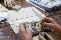 Женщина меняет валюту в обменном пункте в Каракасе. 24 февраля 2015 года. Курс доллара к корзине основных валют держится вблизи 11-летнего максимума и продолжит рост, если выходящий в пятницу отчет о занятости в США поддержит прогноз повышения процентных ставок ФРС в ближайшие месяцы. REUTERS/Carlos Garcia Rawlins