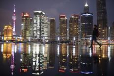 Женщина на набережной Бунд напротив финансового района Пудун в Шанхае. 5 марта 2015 года. Китай должен проводить в этом году бюджетную политику, направленную на поддержание роста, чтобы предотвратить резкое замедление экономики, сказал в пятницу министр финансов Лу Цзивэй. REUTERS/Aly Song