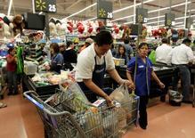 Un trabajador empaqueta unas compras en un supermercado de la cadena Walmart en Ciudad de México, nov 17 2011. La confianza del consumidor mexicano subió en febrero frente a enero, principalmente por la expectativa de una mejor situación económica en el hogar y por la posibilidad en el momento actual de comprar bienes duraderos, dijo el viernes el instituto de estadísticas INEGI. REUTERS/Henry Romero