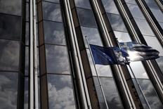 A European Union flag (L) and a Greek national flag flutter as the sky is reflected on a building front in Athens February 17, 2015.  REUTERS/ Alkis Konstantinidis