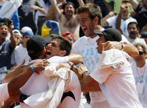 Tenista argentino Delbonis é abraçado pelo capitão da equipe na Copa Davis, Daniel Orsanic, e pelos companheiros Del Potro e Berlocq após vencer o brasileiro Thomaz Bellucci. 09/03/2015 REUTERS/Enrique Marcarian