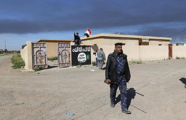 An Iraqi officer walks past a wall painted with the black flag commonly used by Islamic State militants, in the town of Tal Ksaiba, near the town of al-Alam, March 7, 2015. REUTERS/Thaier Al-Sudani