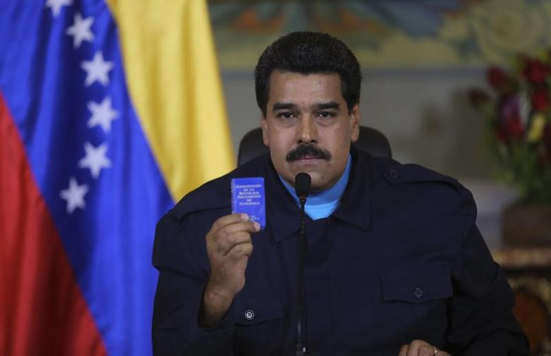 Venezuela's President Nicolas Maduro holds up a book of the country's constitution as he speaks during a national TV broadcast in Caracas in this March 9, 2015 picture provided by Miraflores Palace. REUTERS/Miraflores Palace/Handout via Reuters