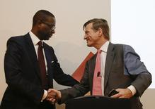 Credit Suisse outgoing Chief Executive Brady Dougan (R) and Tidjane Thiam shake hands after a Credit Suisse news conference in Zurich, March 10, 2015.   REUTERS/Arnd Wiegmann