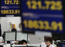 Empleados de una firma de comercio de divisas trabajan bajo monitores que muestran el tipo de cambio del yen japonés frente contra el dólar (arriba) y el índice Nikkei de la bolsa de Tokio, 10 de marzo del 2015. Las bolsas de Asia operaban el miércoles en mínimos de dos meses en medio de la inquietud sobre una subida anticipada de las tasas de interés de Estados Unidos, una perspectiva que hizo que el dólar anotara un máximo en 12 años frente al euro. REUTERS/Toru Hanai