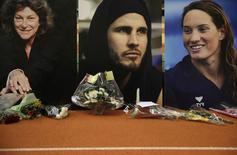 Retratos dos três atletas mortos, durante tributo em Paris.    11/03/2015   REUTERS/Christian Hartmann