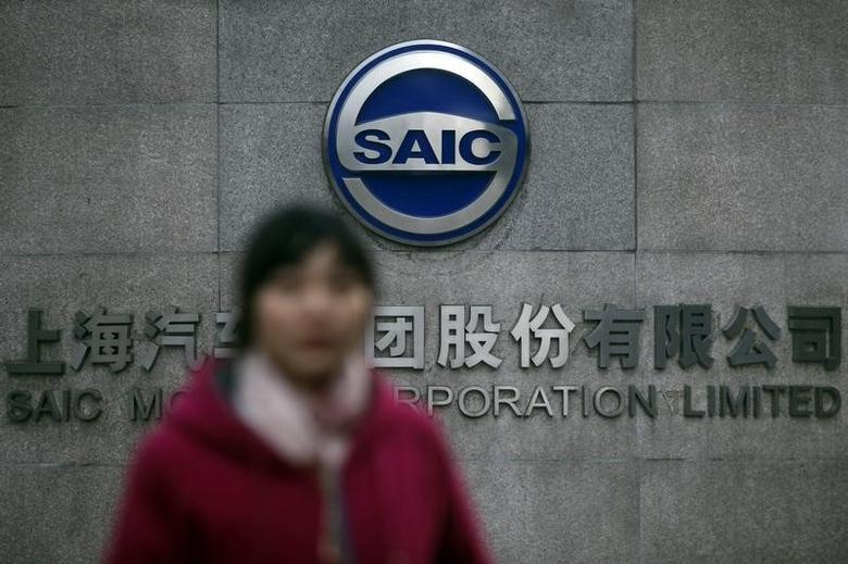 A woman walks past the gate of SAIC Motor Corporation Limited in Shanghai January 26, 2013.   REUTERS/Aly Song