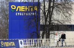 Прохожие у супермаркета Лента в Москве. 3 февраля 2014 года. Один из крупнейших в РФ продуктовых ритейлеров Лента, чья чистая прибыль во втором полугодии 2014 года прибавила 39 процентов в рублях, нарастил продажи с начала текущего года, а по итогам всего 2015-го ждет рост выручки на 34-38 процентов. REUTERS/Maxim Shemetov